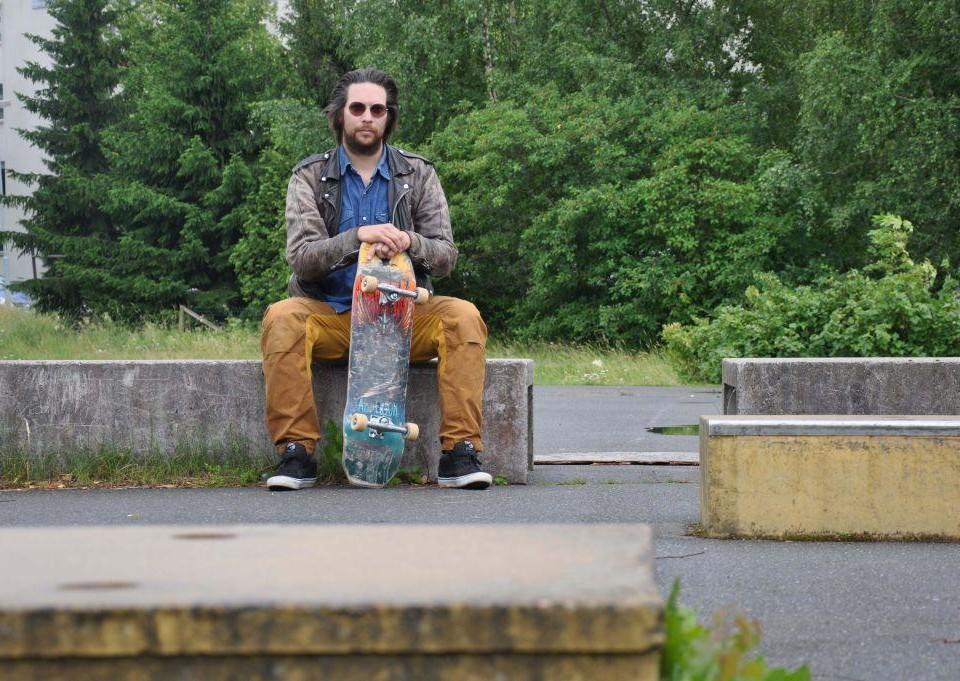 Man sitter med skejtboard i skejtpark