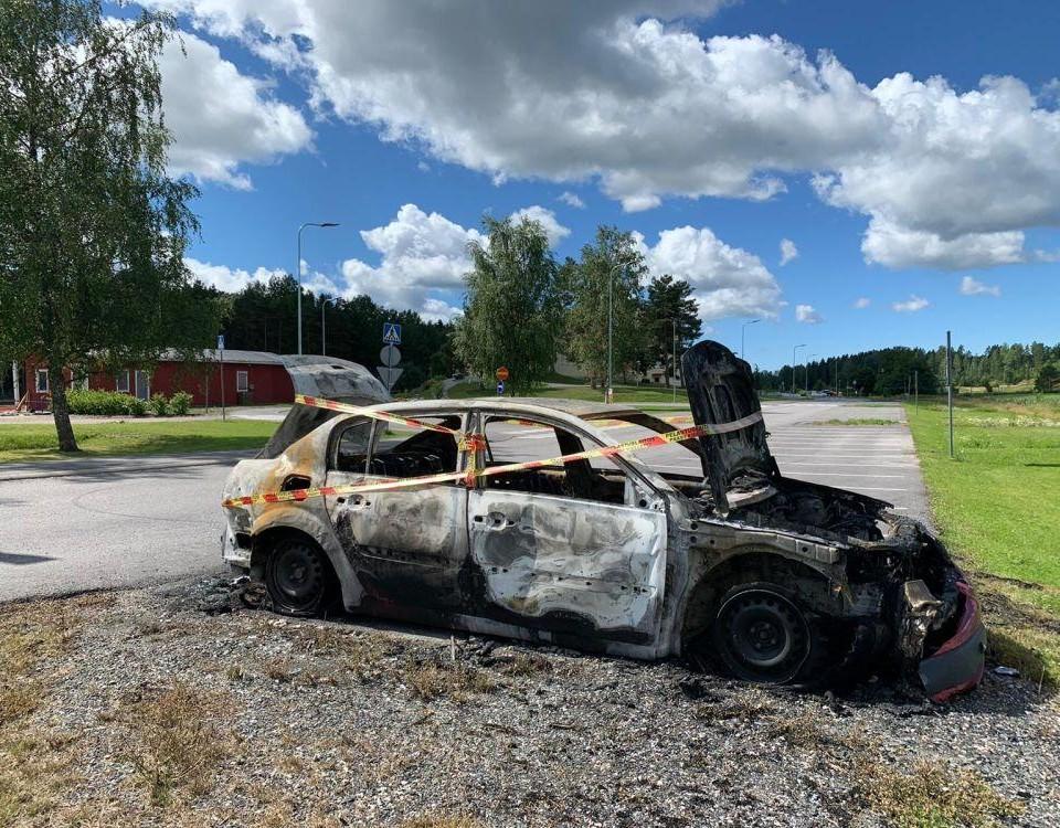 En brunnen bil inlindad i varningstejp på en annars tom parkeringsplats.