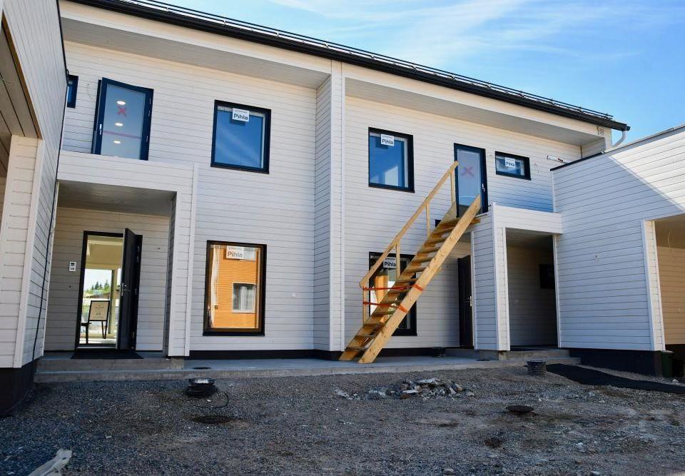 Nybyggt, vitt tvåvåningshus i trä.