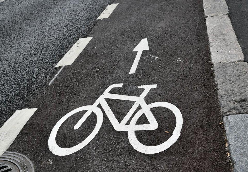 En cykelfil vid sidan av en bilväg med bilden av en cykel målad i vitt.