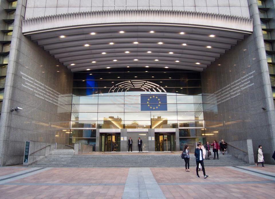En massiv ingång till stor och modern byggnad med EU:s flagga på.