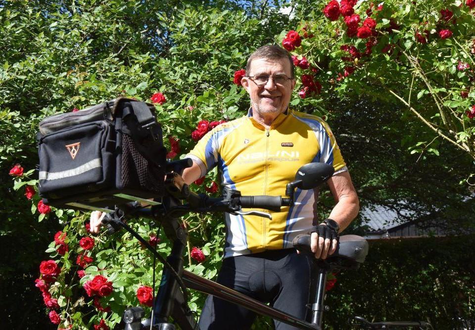 Äldre man iklädd gula cykelkläder håller i en cykel framför en rosenbuske.