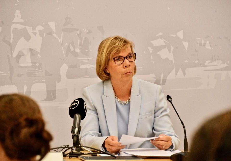 Porträtt av kvinna som sitter vi bord framför mikrofon.