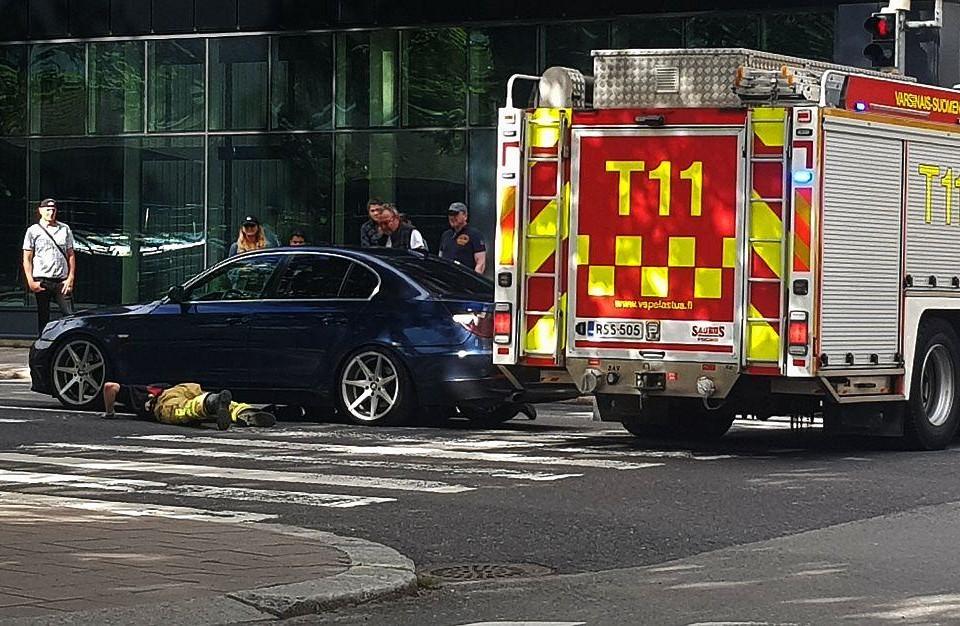 Brandman ligger vid bil i korsning