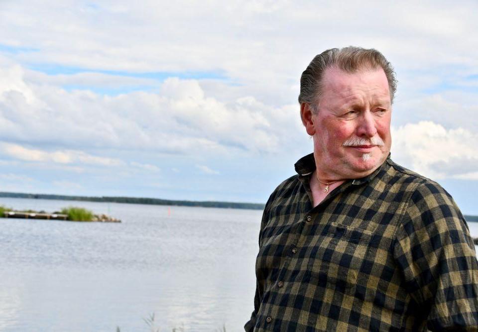 Porträtt av äldre man klädd i flanellskjorta med ett hav i bakgrunden.