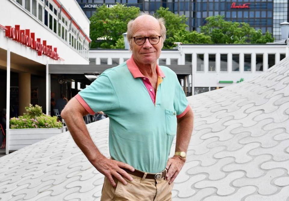 Porträtt av äldre man klädd i avslappnade kläder i en urban miljö.