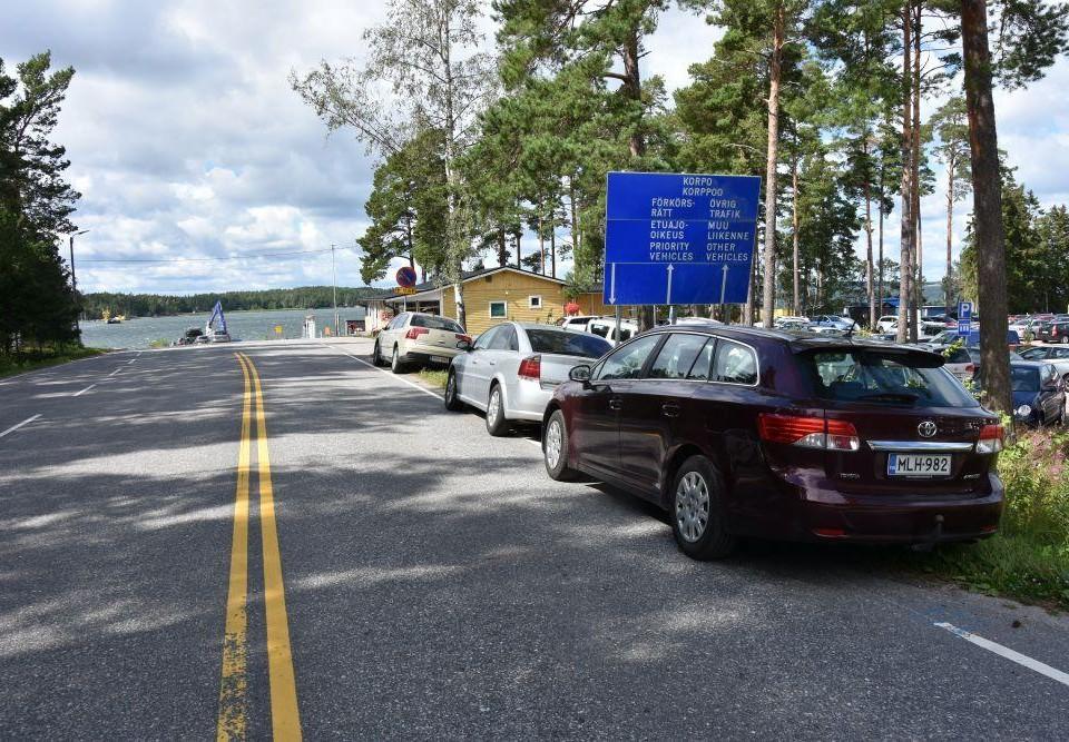 Bilar parkerade vid en vägren. Intill bilarna finns en skylt med information om färjtrafiken till Korpo och i bakgrunden syns havet och en färja som närmar sig stranden.