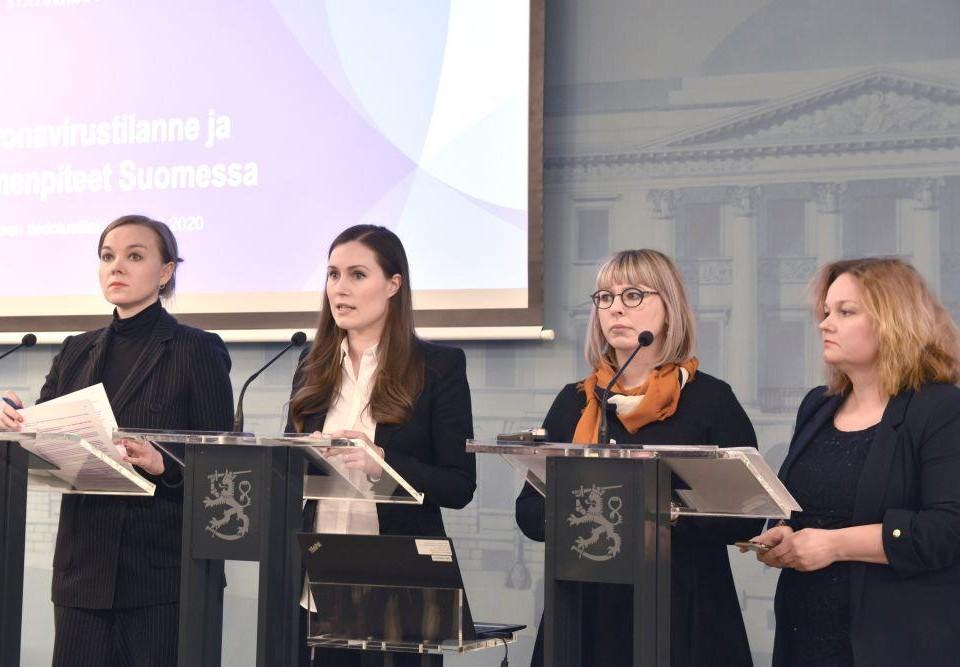 Fyra formellt klädda kvinnor står framför podium med mikrofoner och ser seriösa ut.