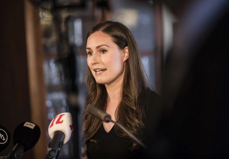 Kvinna talar i flera mikrofoner som sträcks fram emot henne.