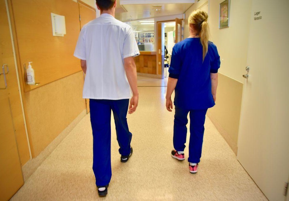 Ryggen av två personer klädda i vårdpersonalskläder i en sjukhuskorridor.