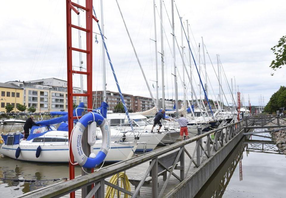 En rad med segelbåtar förtöjda vid en gästhamn. En person ombord på en av segelbåtarna räcker något till en person som står på bryggan.
