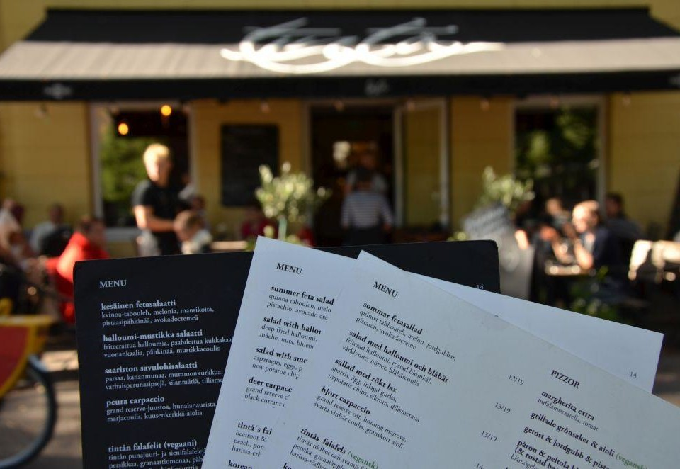 Tre menyer, en på svenska, en på engelska och en på finska i fokus framme i bilden. Ur fokus i bakgrunden ser man ingången till restaurangen Tintå och kunder på restaurangens terass.