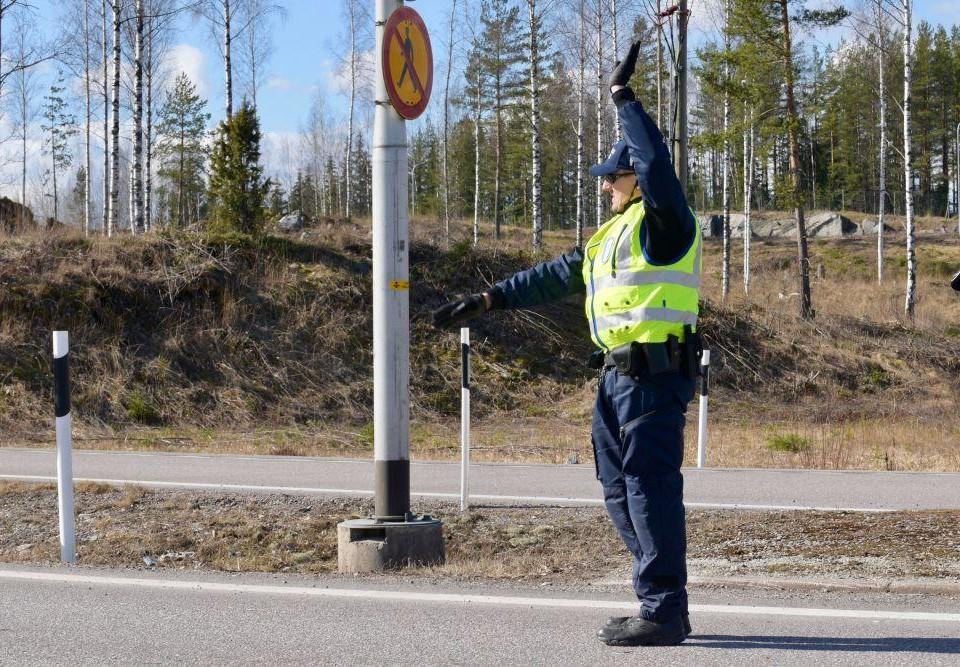 En polis klädd i en gul skyddsväst lyfter handen för att stanna en bil som inte syns i bilden.