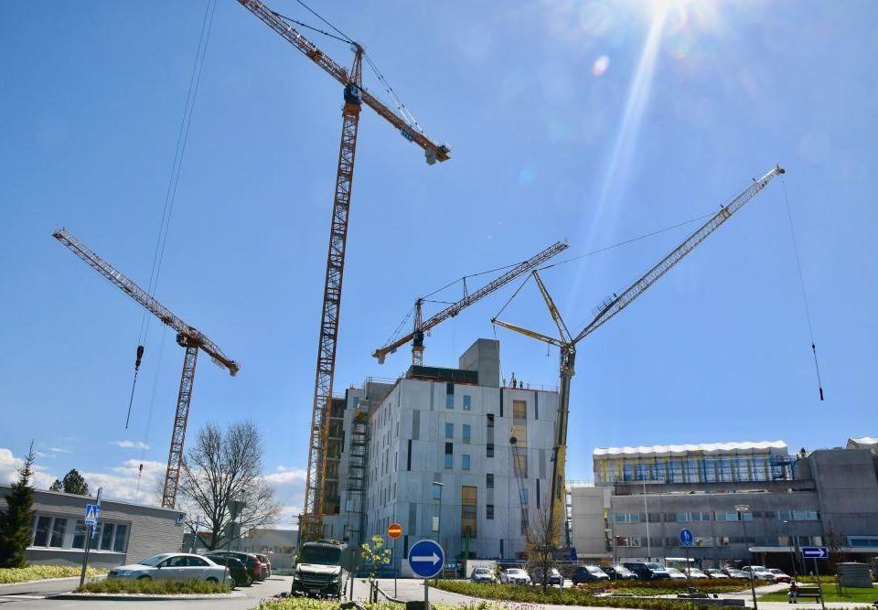 En byggarbetsplats med flera lyftkranar under en blå himmel.