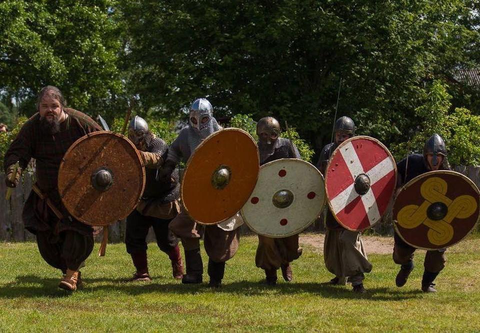 En grupp människor klädda i vikingakläder och bärandes sköldar springer över en gräsmatta.