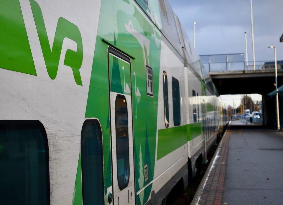 """Sidan av ett vitt tåg med gröna dekorationen och texten """"VR"""" skriven i grönt på sidan."""