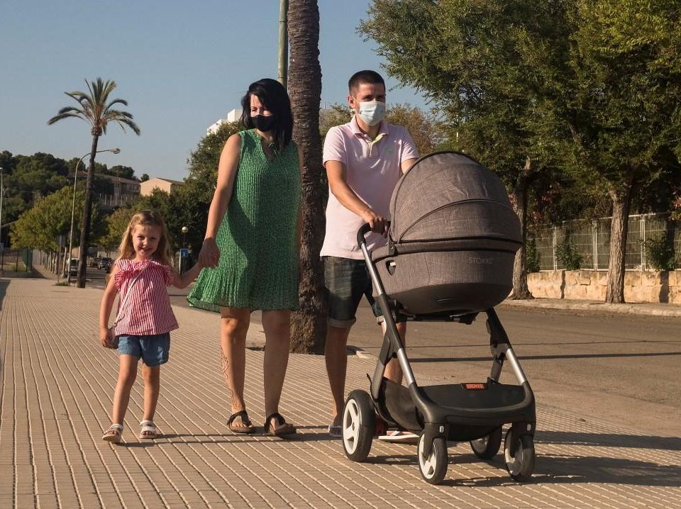 fyrapersoners familj på promenad där palmer vajer i bakgrunden