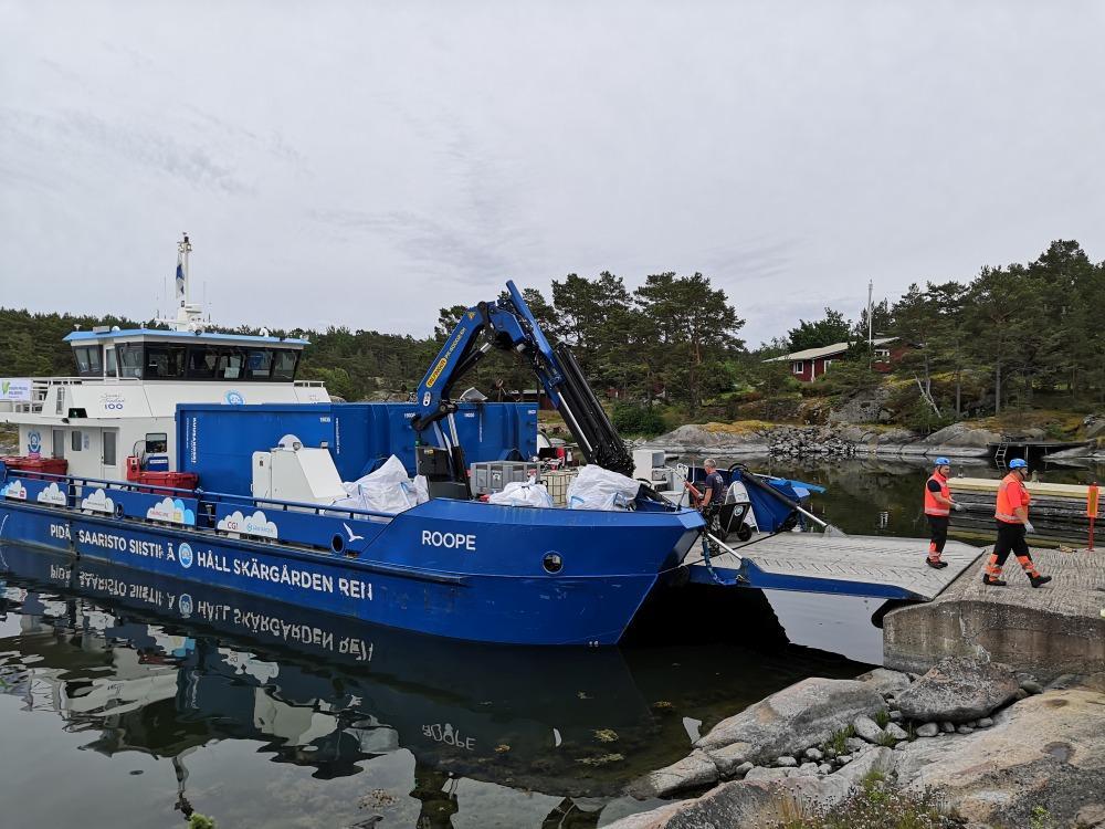 Blått fartyg tar emot skrot i skärgården