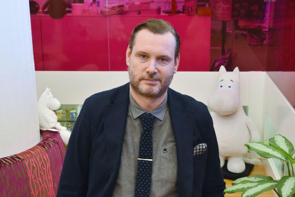 En man med en muminfigur i bakgrunden.
