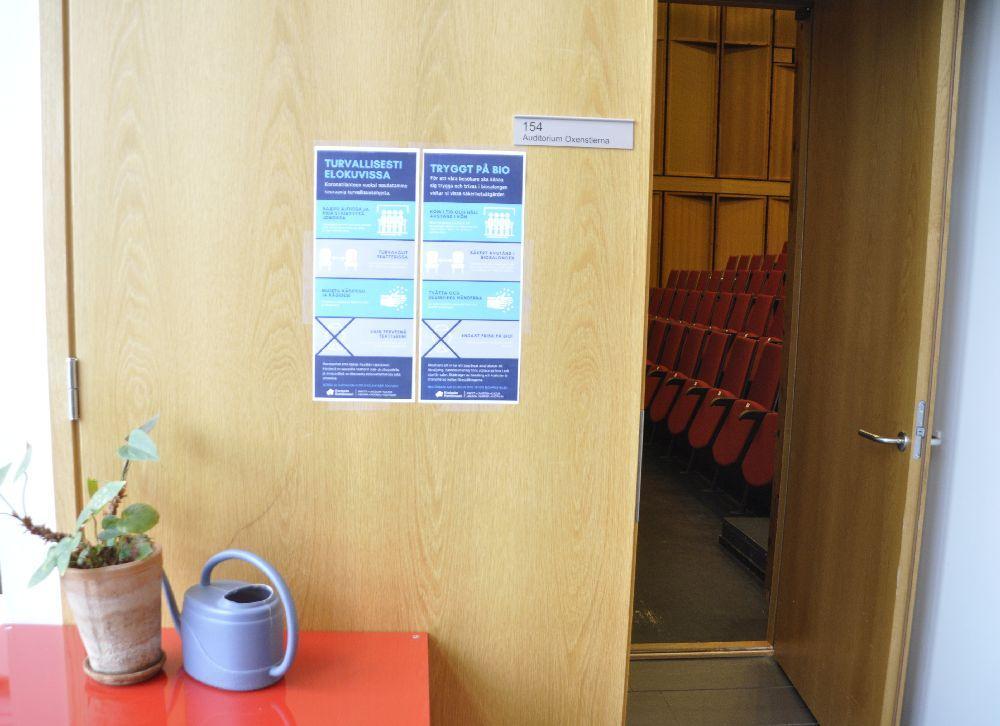 En dörr med plakat om en trygg bioupplevelse. Genom en öppen dörr syns auditoriet med röda stolar.