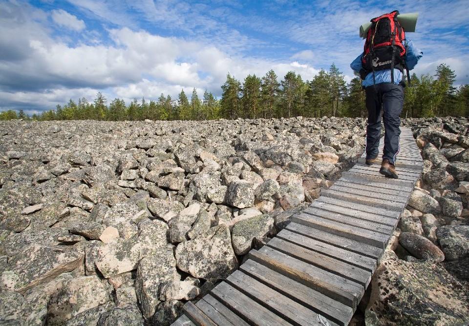 vandrare går på en broförsedd gång bland massor av stenar
