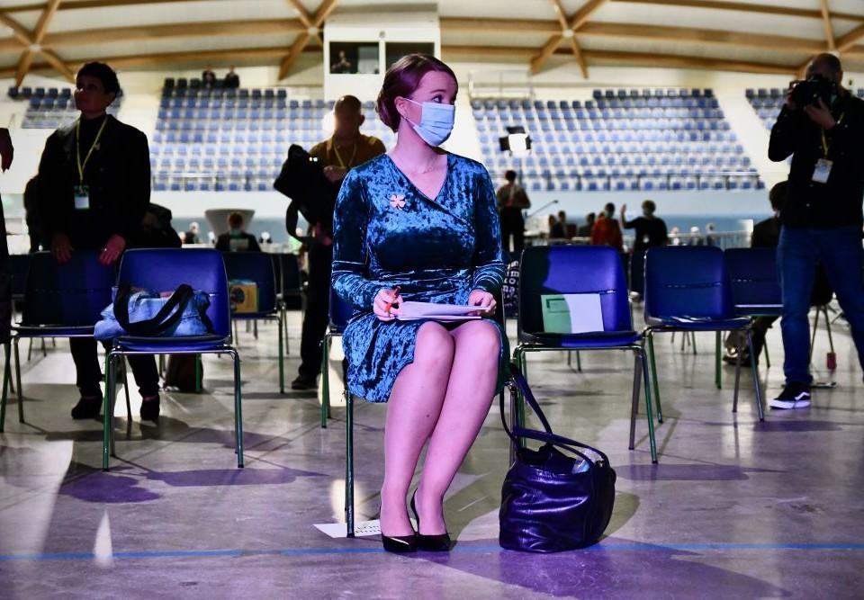 Kvinna med munskydd i en stor sal.