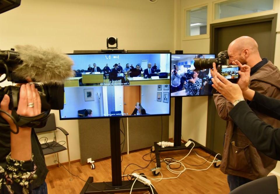 Journalister fotograferar en rättegång via en skärm.