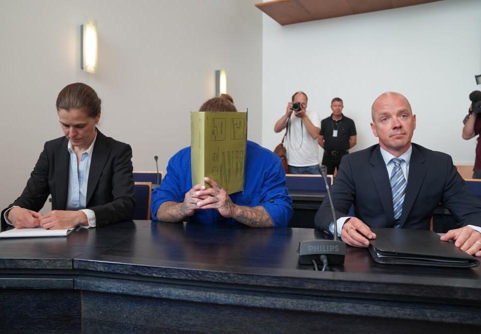 Männsikor i en rättssal där en person döljer sitt ansikte med en bok.