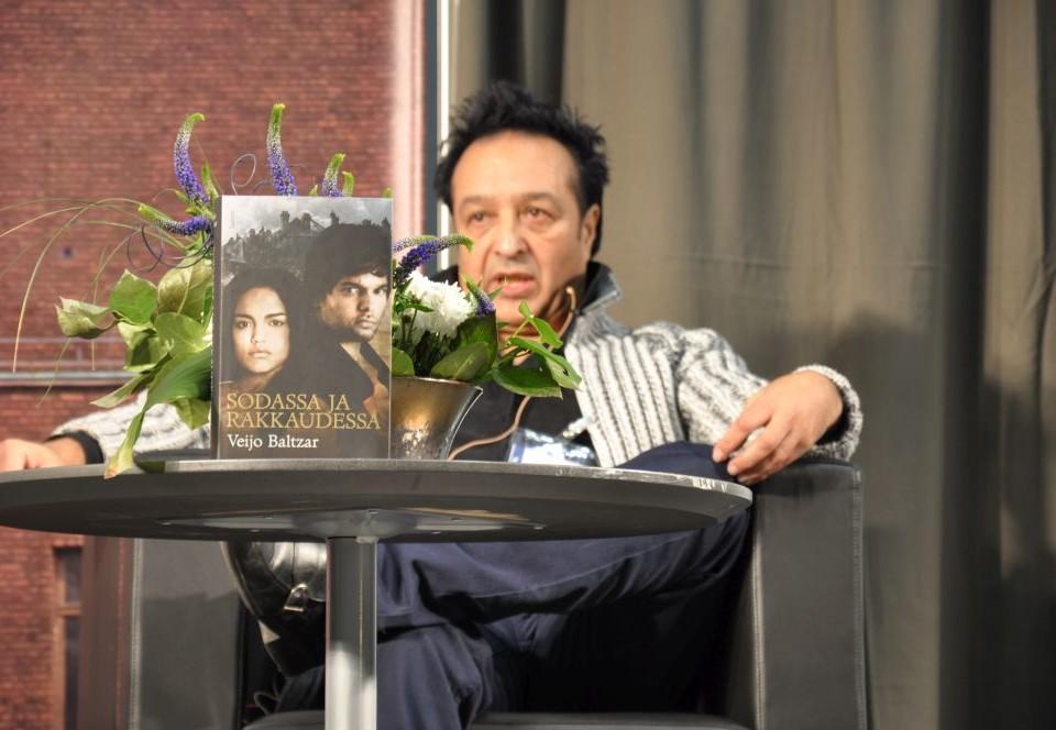 Man som sitter vid ett bord med blommor.