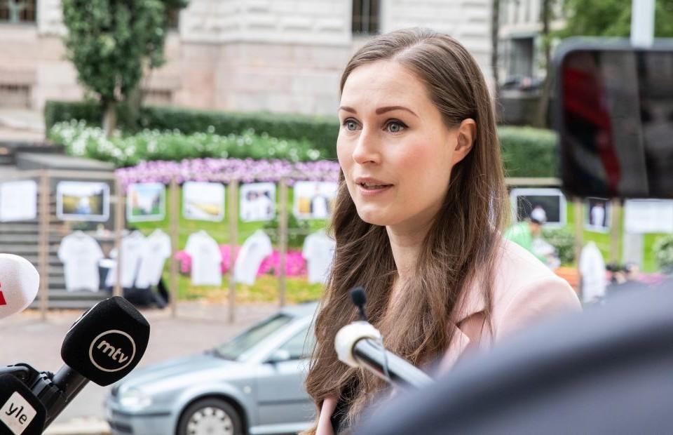 Kvinna med mörkt långt hår framför mikrofoner.