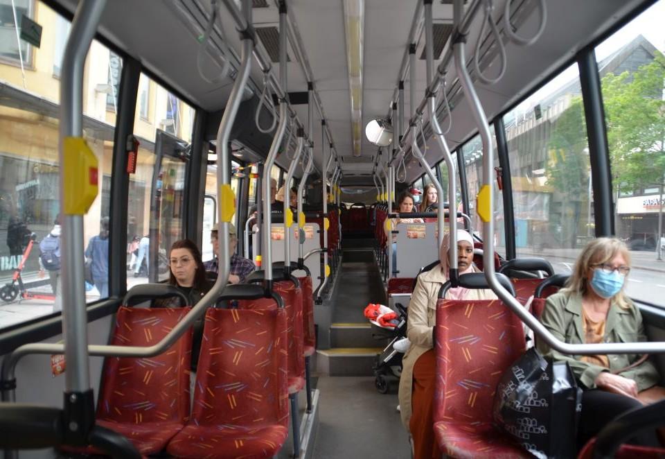 Passagerare på en buss. En person har munskydd.