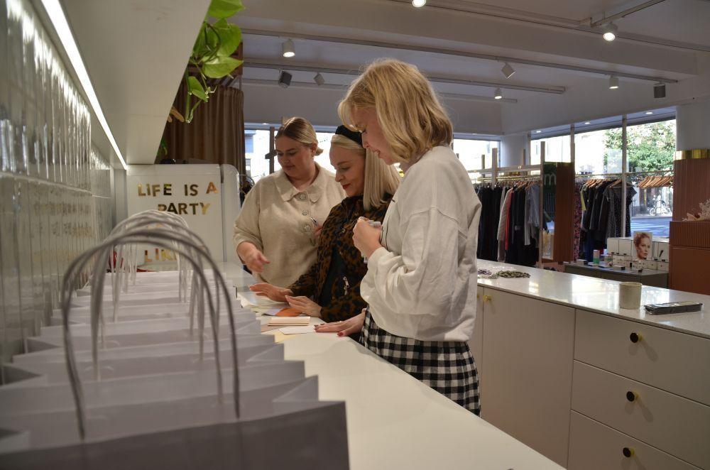 Tre kvinnor står vid en disk i en affär.