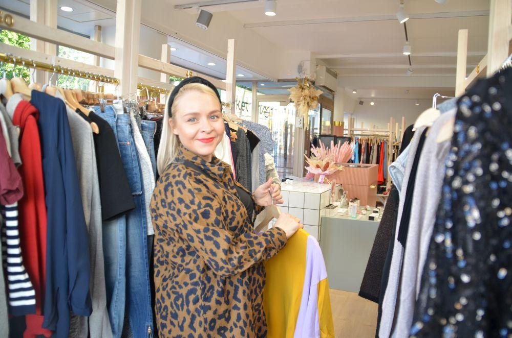 Ung kvinna bland kläder i en affär.
