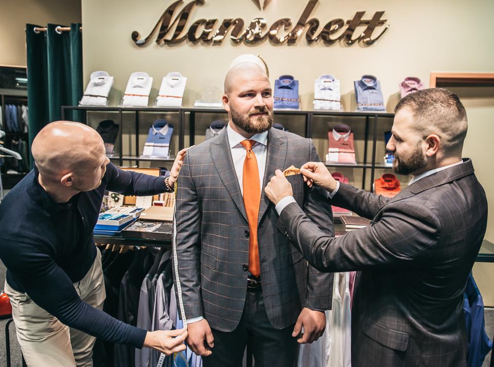 två herrar mäter tredje herre för kostymprovning