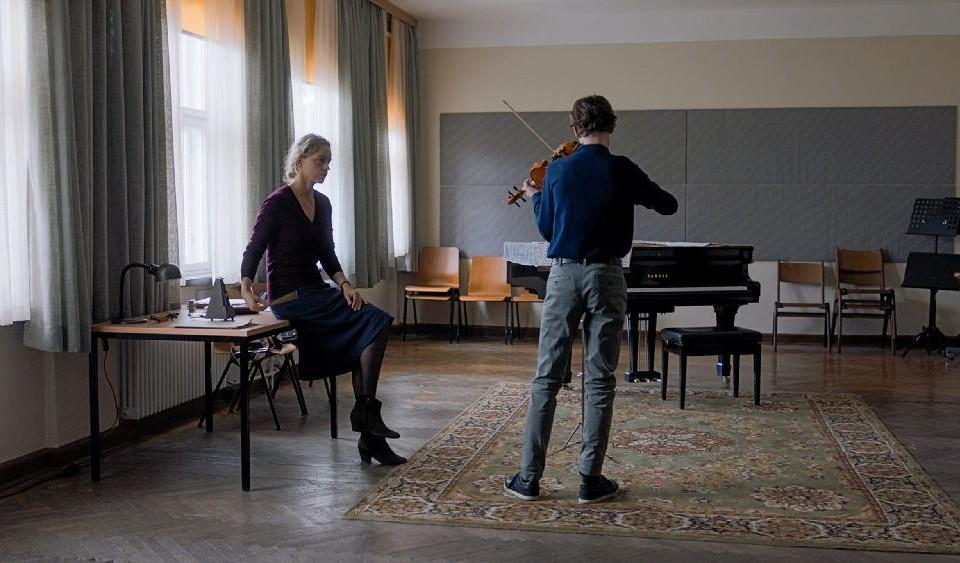 Ur en film. Två personer i ett rum, den ena spelar fiol.