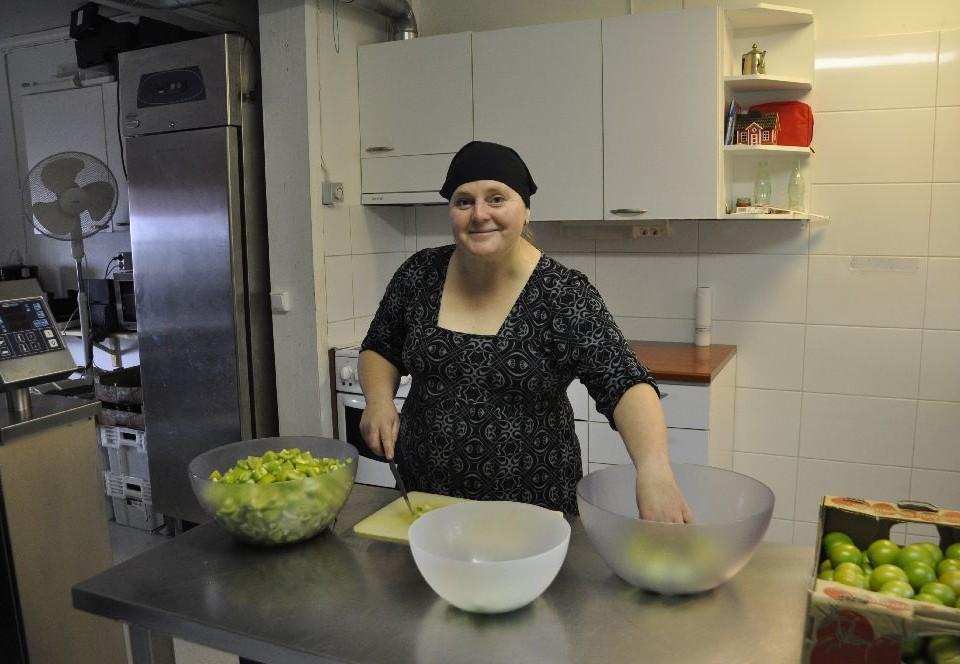 Dam i professionellt kök. På bordet skålar och en låda med gröna tomater.