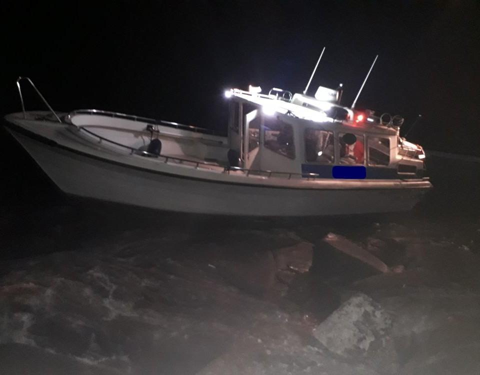 En motorbåt på stenar i natten.