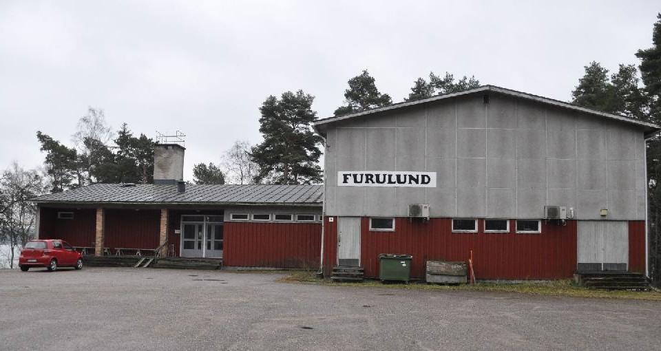 """Stort föreningshus i grått ocg vitt, med skylten """"Furulund"""""""
