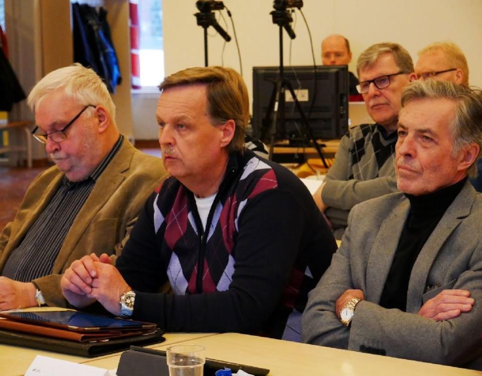 Tre män sitter i rad i en fullmäktigesal