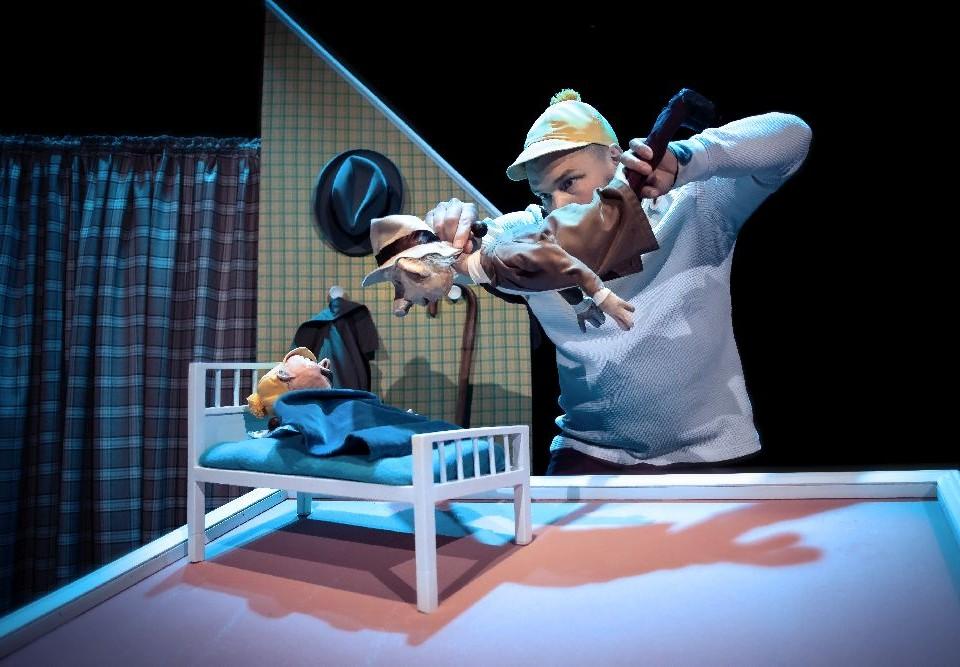 Man på en scen med två dockor