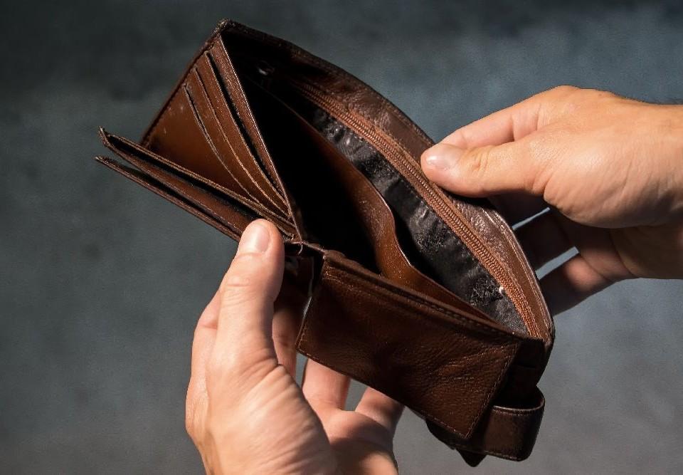Händer öppnar en tom plånbok.