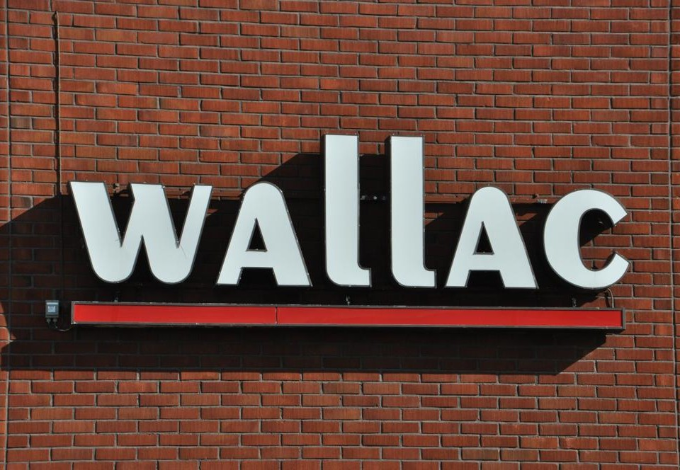 En logga med texten Wallac på en tegelvägg.