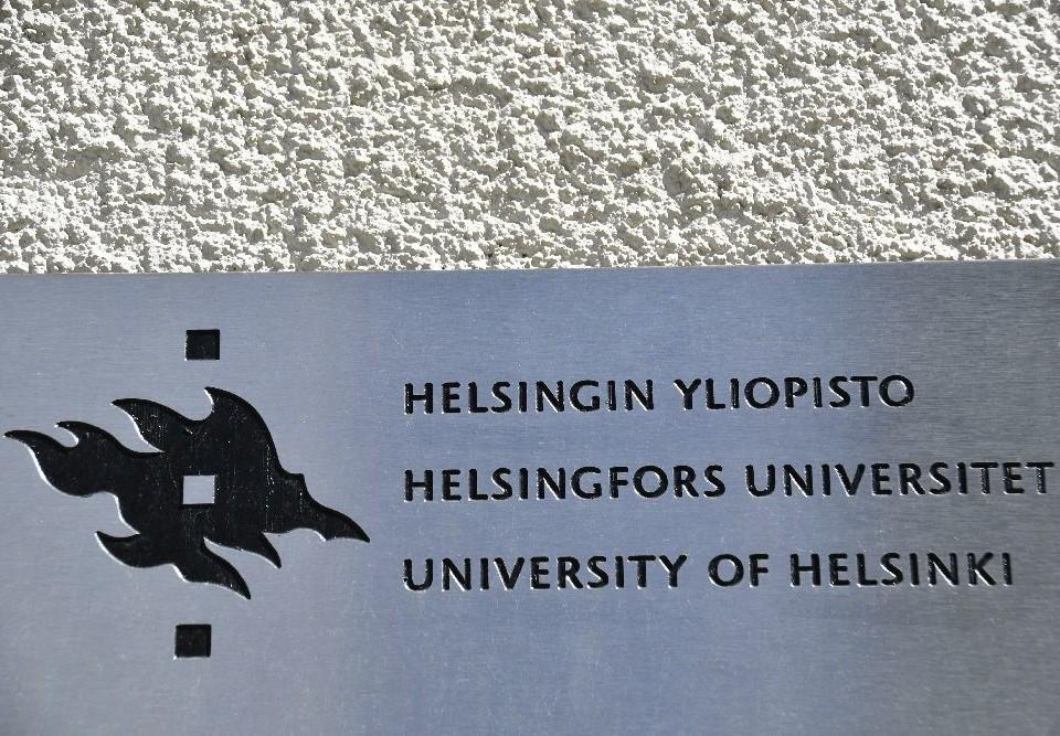 Liten skylt på byggnad med texten Helsingfors universitet på 3 språk.