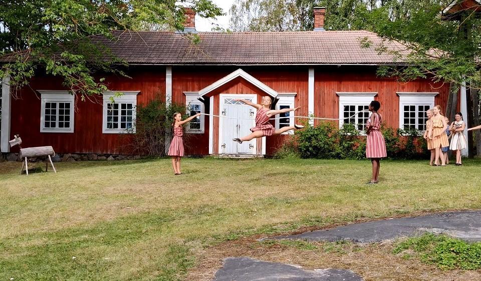 Flickor dansar på gräsmattan framför gammalt hus