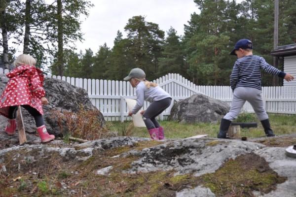 Tre barn leker med träbitar bland stenar på en bakgård, Daghemmet Karusellen i nagu