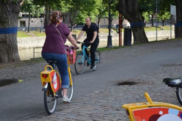 kvinna cyklar iväg på en stadscykel längs auraå
