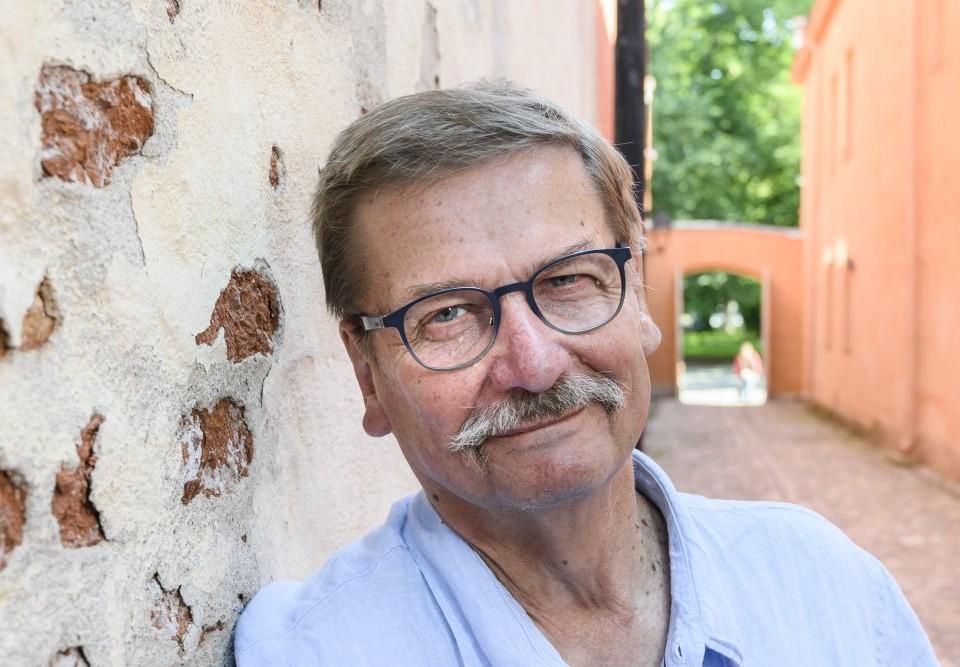 man med glasögon och mustash, kari j. kettula, lutar mot en vägg