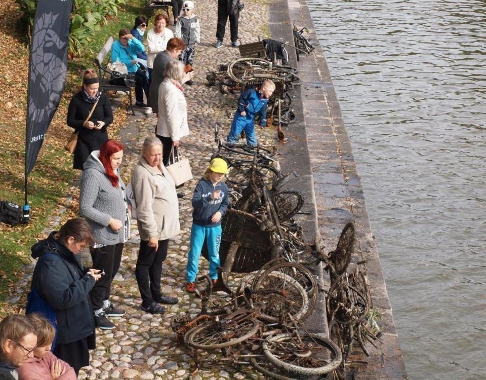 folk står vid aura å med uppfiskade rostiga cyklar