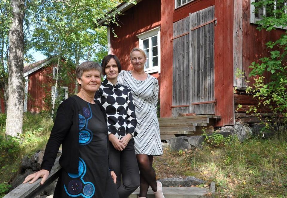 tre kvinnor vid ett gammalt hus