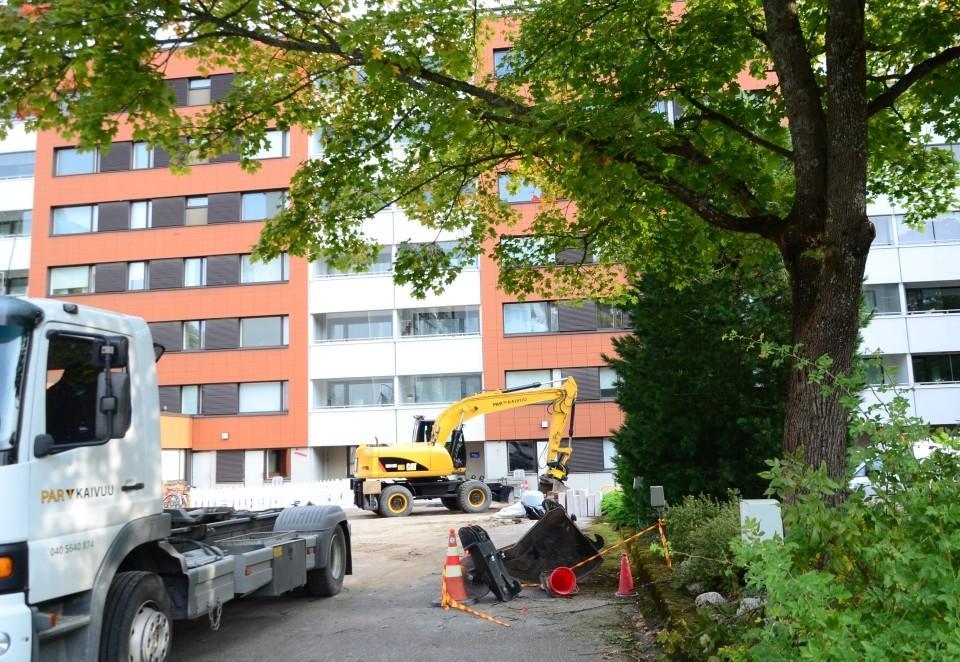 våningshusgård med lastbil och grävskopa på gården